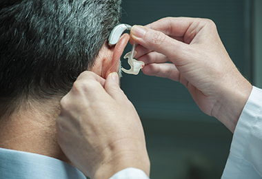 doctor placing hearing aid to a patient