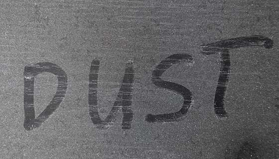 a dusty table with the word dust spelled out