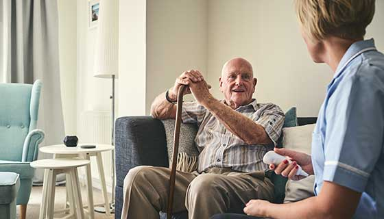 senior man with cane smiling at caretaker