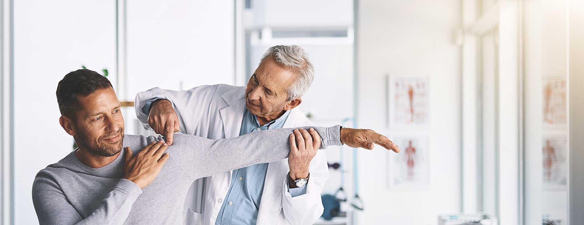 a doctor checks the shoulder and arm joints of male patients