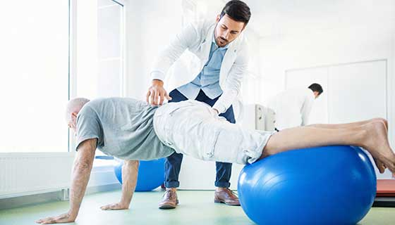 Senior man in physical therapy for back pain