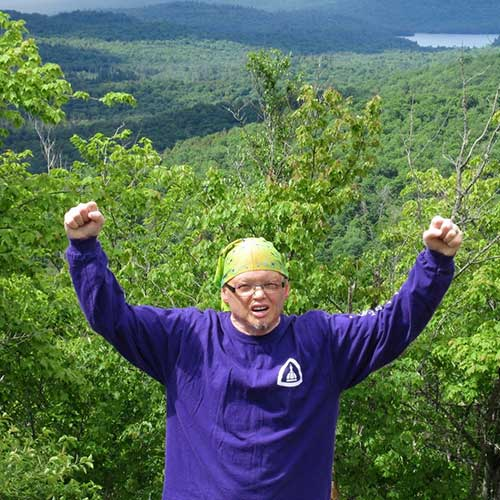 Craigs throws his hands in the air in celebration at the summit of a hiking trail.