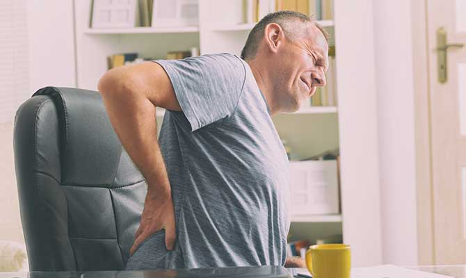 Man at his desk suffering from back pain