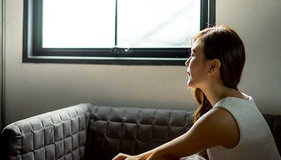 A woman sits alone, looking out a window.
