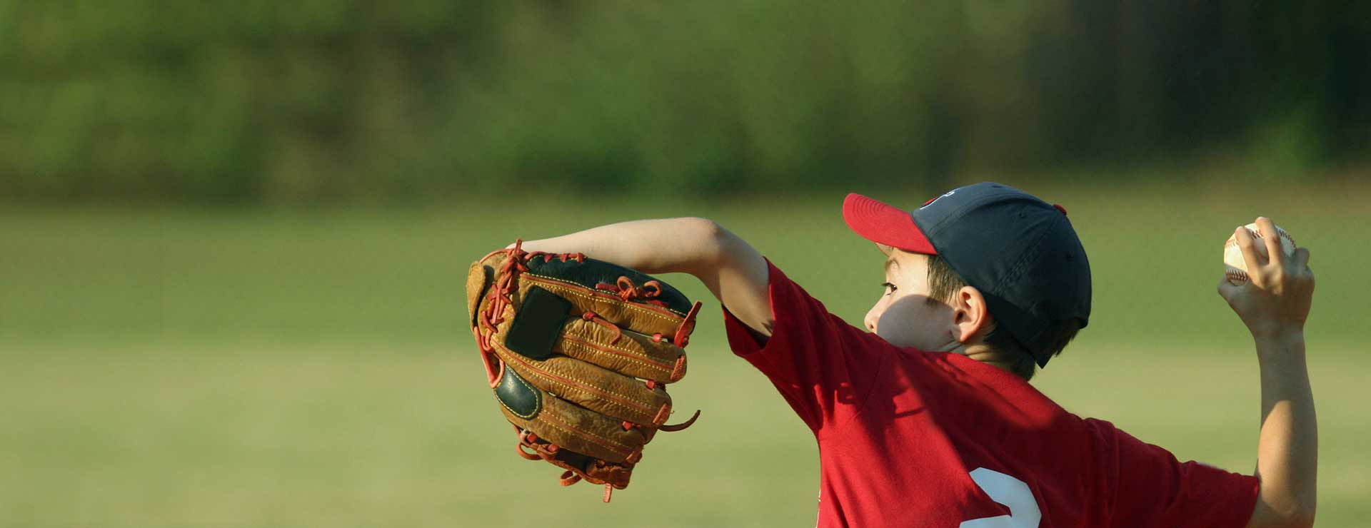 A young boy winds up his arm to pitch a baseball.