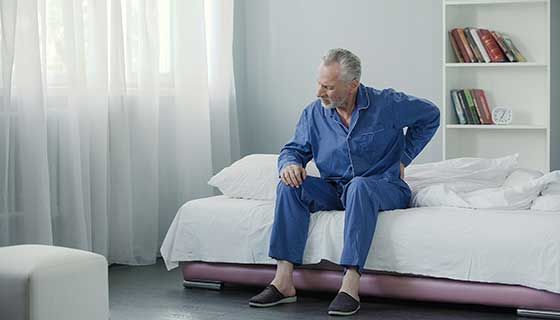 A man experiences back pain while getting out of bed.