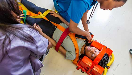 A woman is placed onto a stretcher.