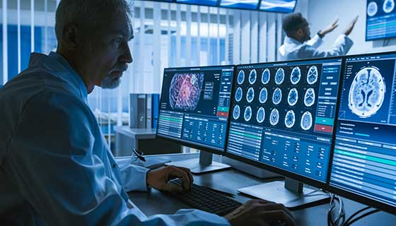Brain surgeon looking at a brain scan on his computer