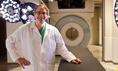 Dr. Henry Brem standing in front of an MRI machine.