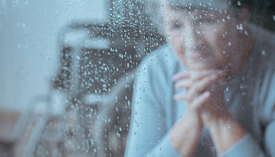 woman looking out a rainy window