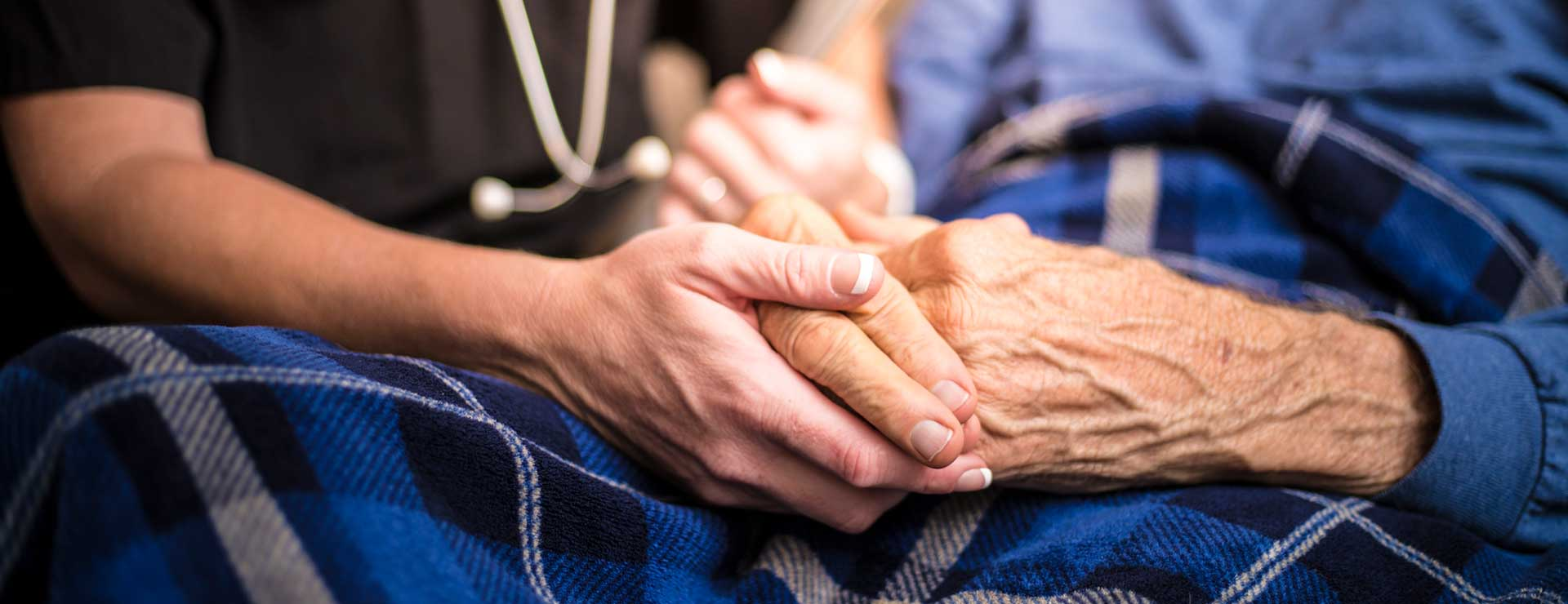 hospice nurse holding elderly patient's hand