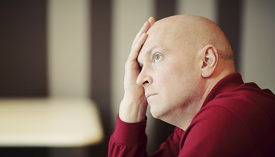 A bald man in a red shirt holds his hand to his forehead, looking preoccupied.