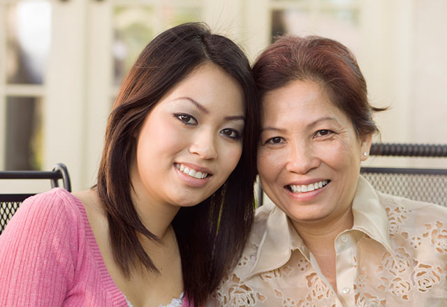 Mother and daughter smiling face side by side