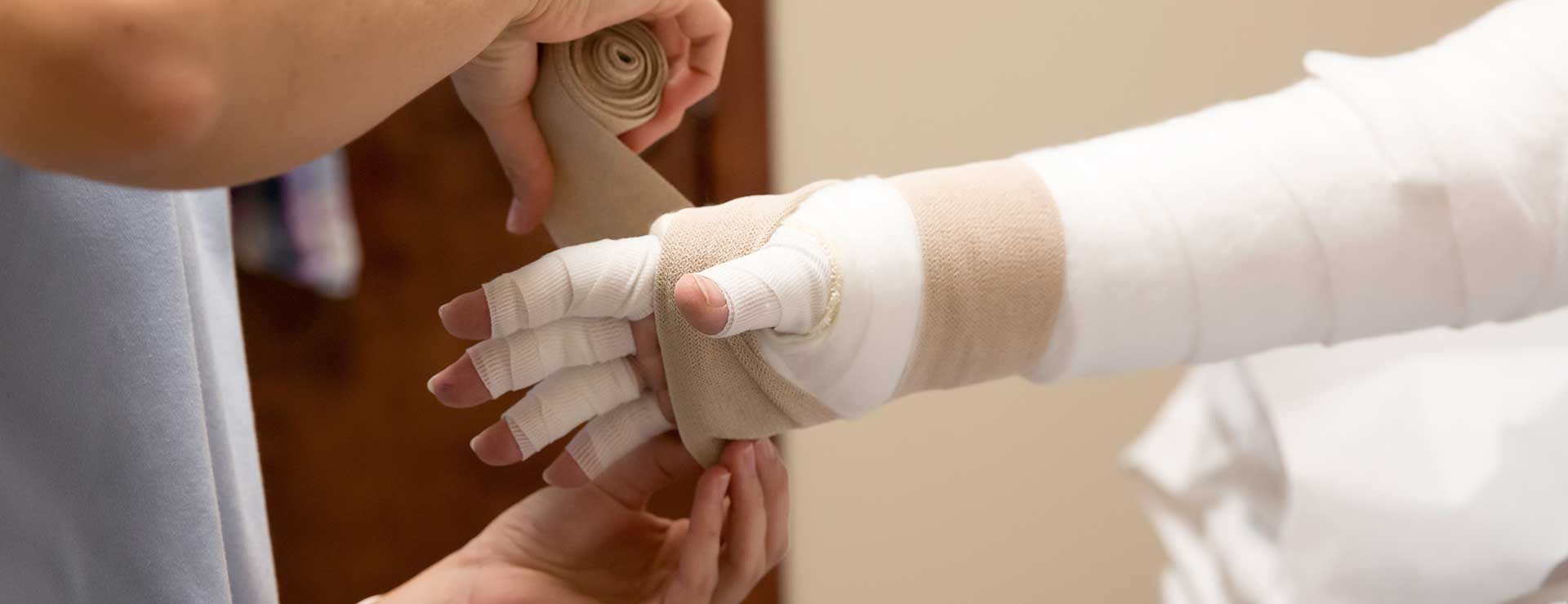 A lymphedema patient gets their arm bandaged.