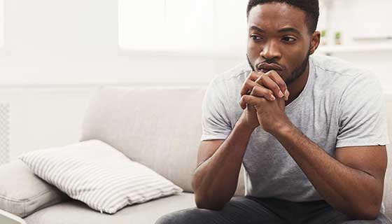 A young man sits pensively on the couch.
