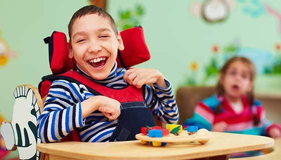 A young boy with cerebral palsy smiles.