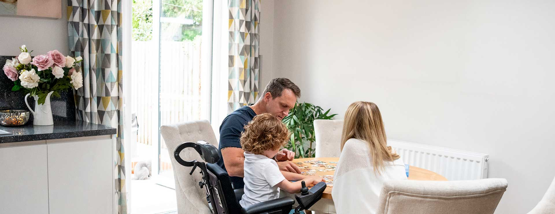 Child with muscular dystrophy with parent's doing a puzzle at table