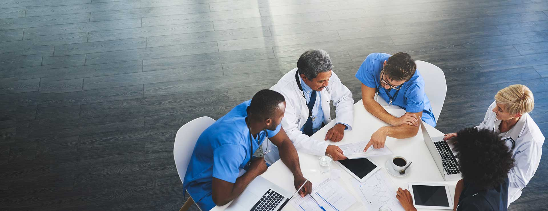 A multidisciplinary team sit around a table, discussing a patient's treatment options.