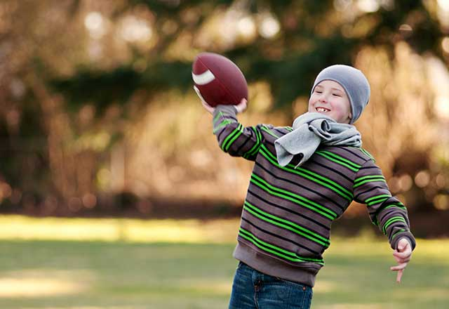 Boy throwing a football outside during winter