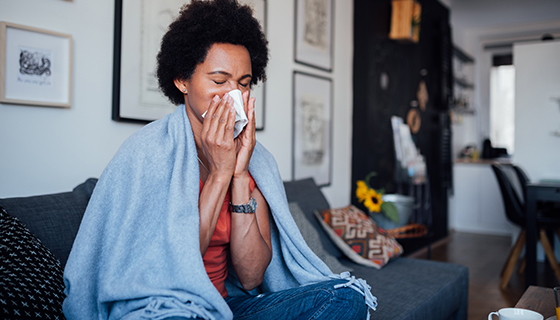 A woman blows her nose while wrapped in a blanket, sitting on her couch.