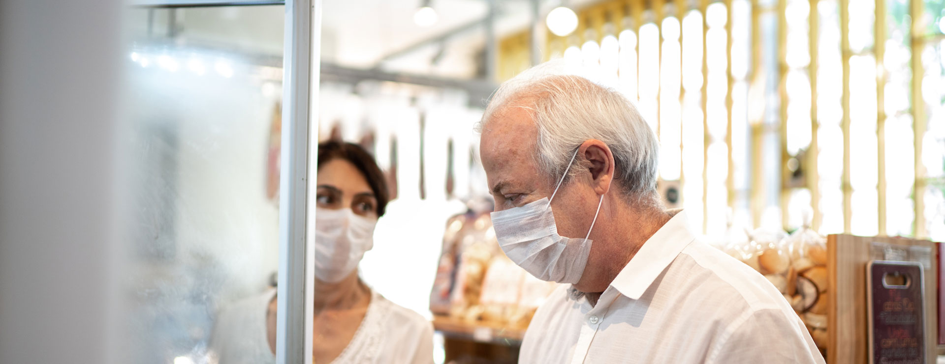 senior couple wears protective masks while shopping