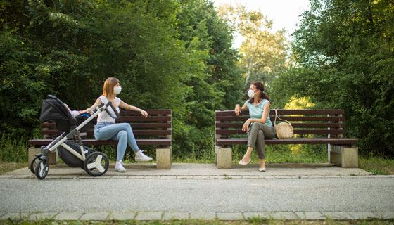Two women have a talk in the park while wearing masks and social distancing