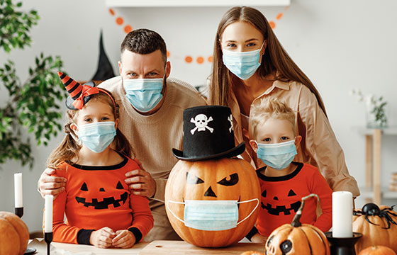 family wearing masks poses with a mask-wearing jack-o-lantern