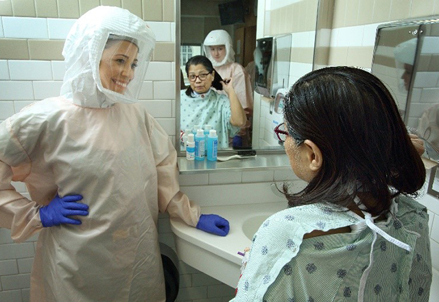 An occupational therapist wearing PPE looks on as a patient brushes her hair.