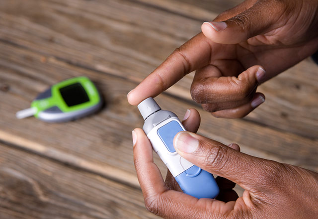 A person with diabetes uses their glucose meter