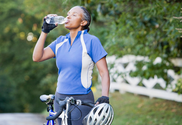 Woman on a bike takes a sip of her water bottle while biking through a wooded area.