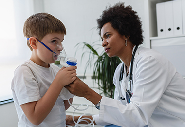 doctor assisting pediatric patient with oxygen mask