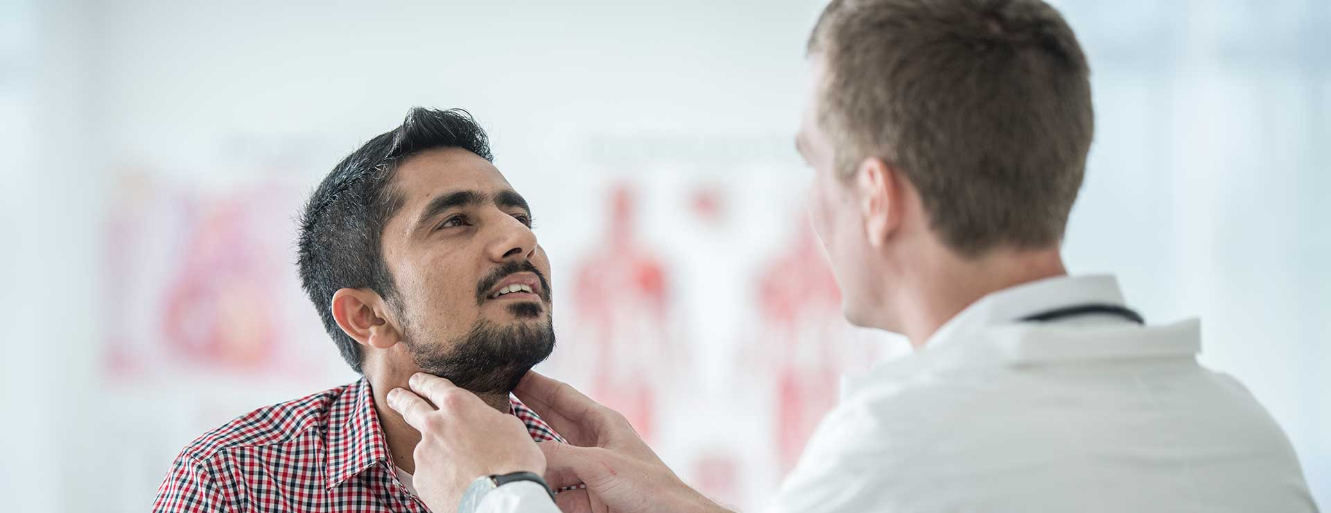 a doctor feels the neck area of male patient to check thyroid