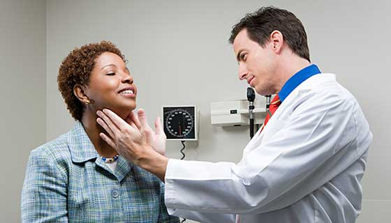 doctor checking thyroid glands of female patient
