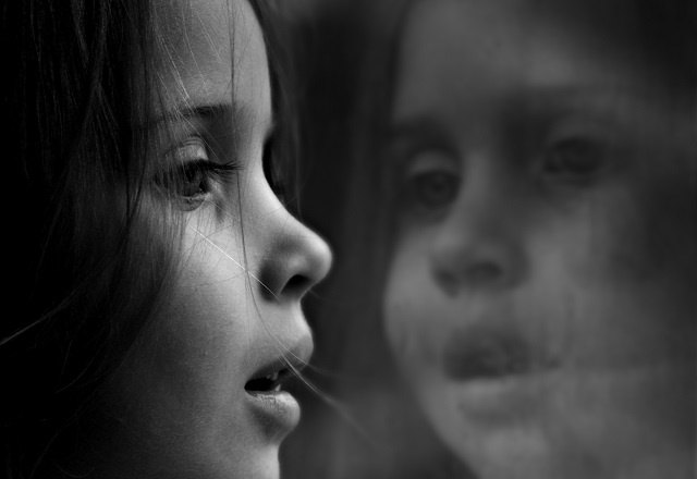 Black and white photo of little girl staring out a window