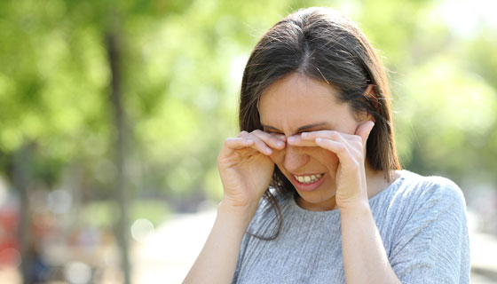 A woman rubs her eyes while outdoors.