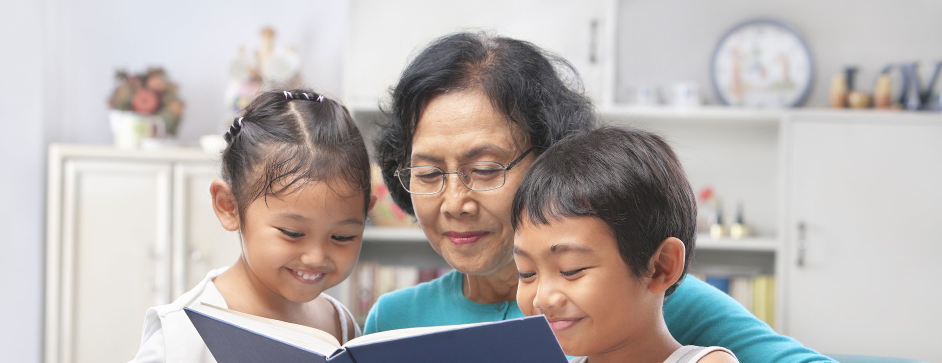A grandmother with glasses reads to her grandchildren