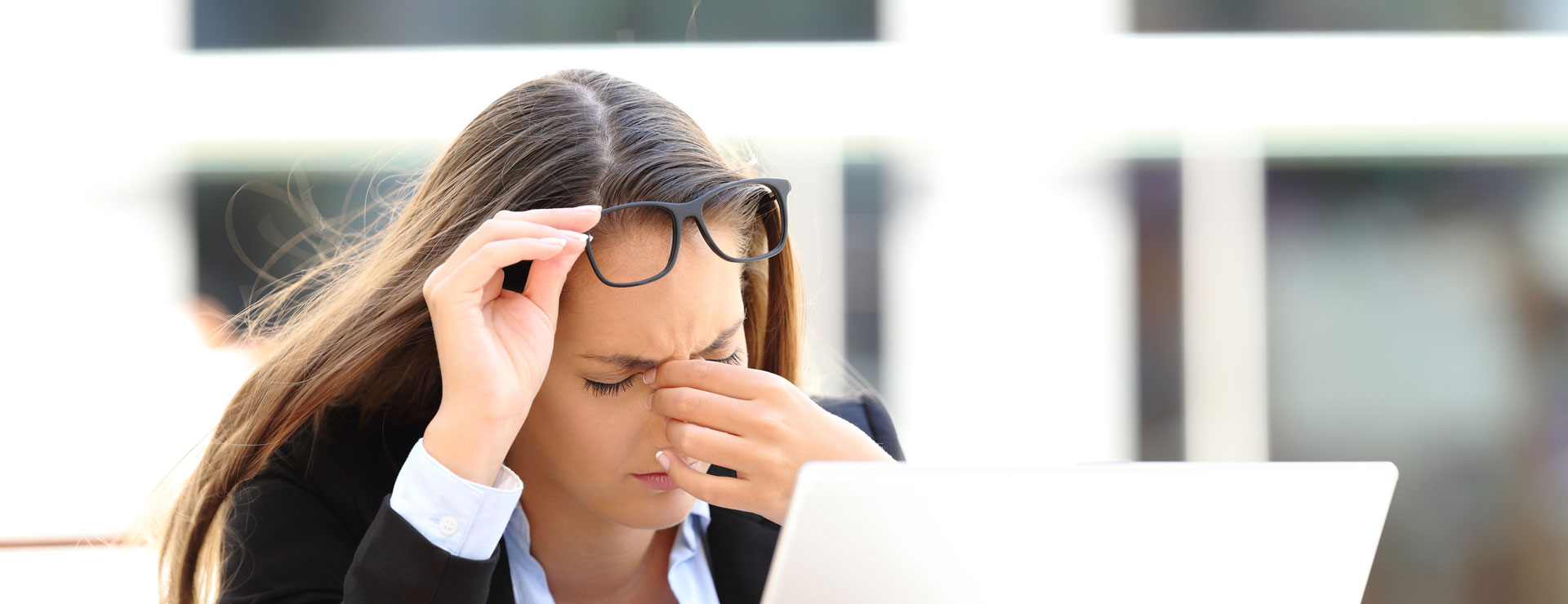 A woman in front of a laptop rubbing her eyes