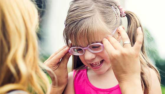 A mother adjusts her daughter's glasses.