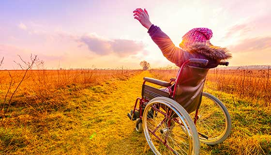 girl in wheelchair outside with arms up in joy