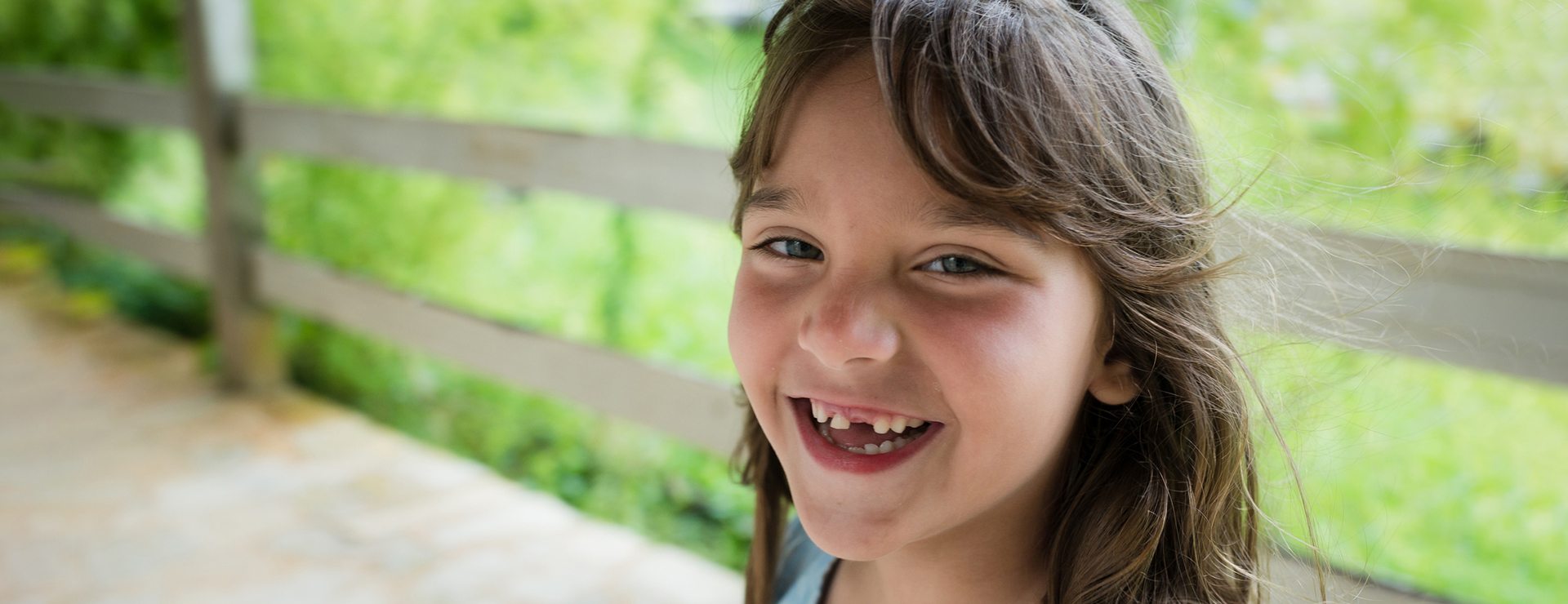 A little girl smiles broadly, showing her missing teeth.