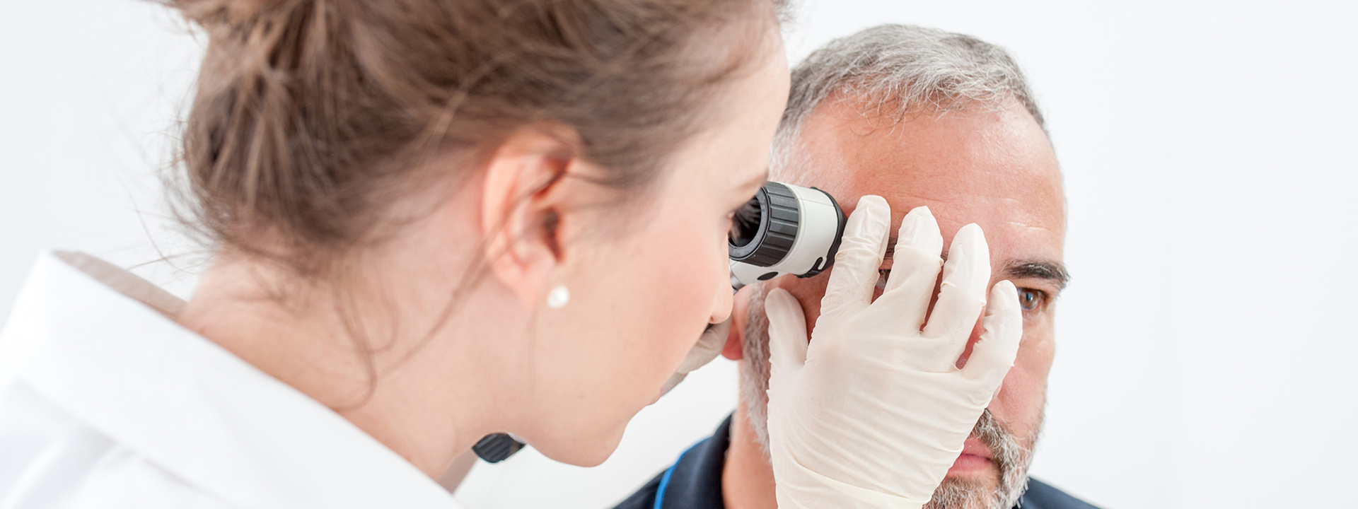 doctor checking patient's skin with magnifier
