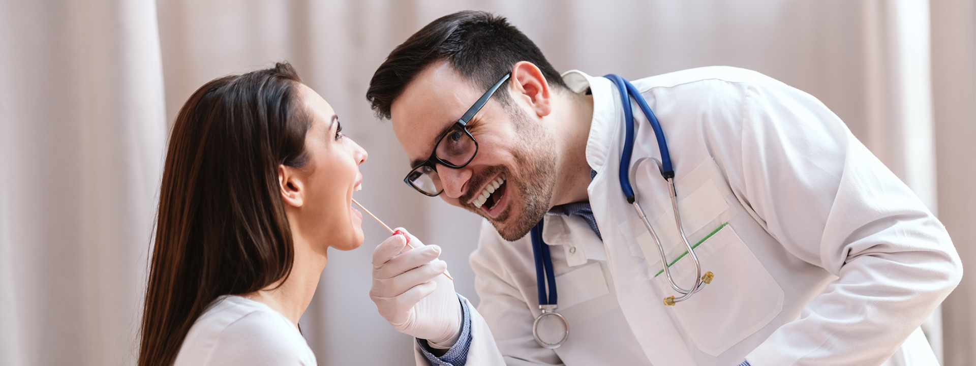 doctor checking young womans throat