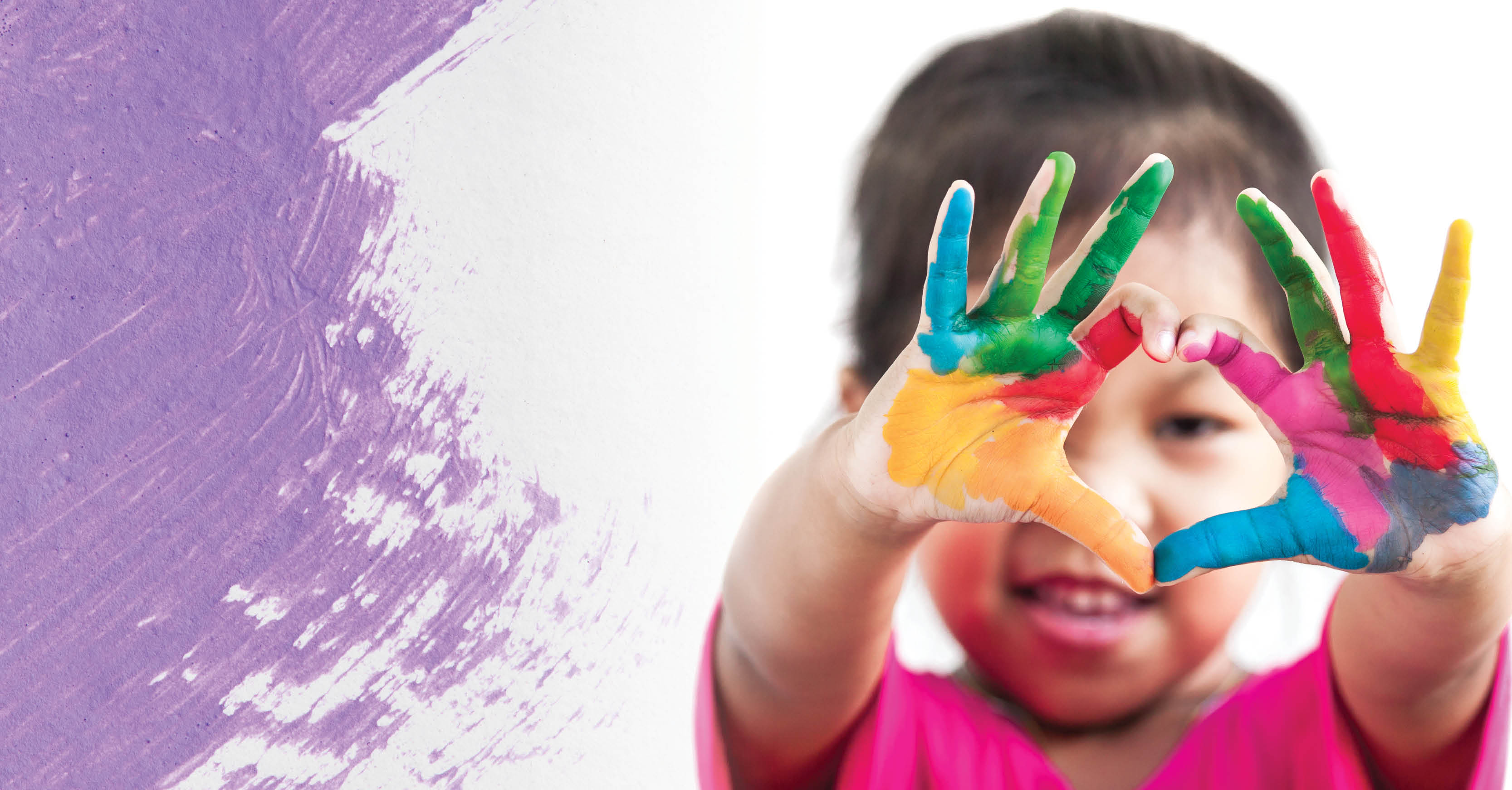 A child makes a heart with their painted hands