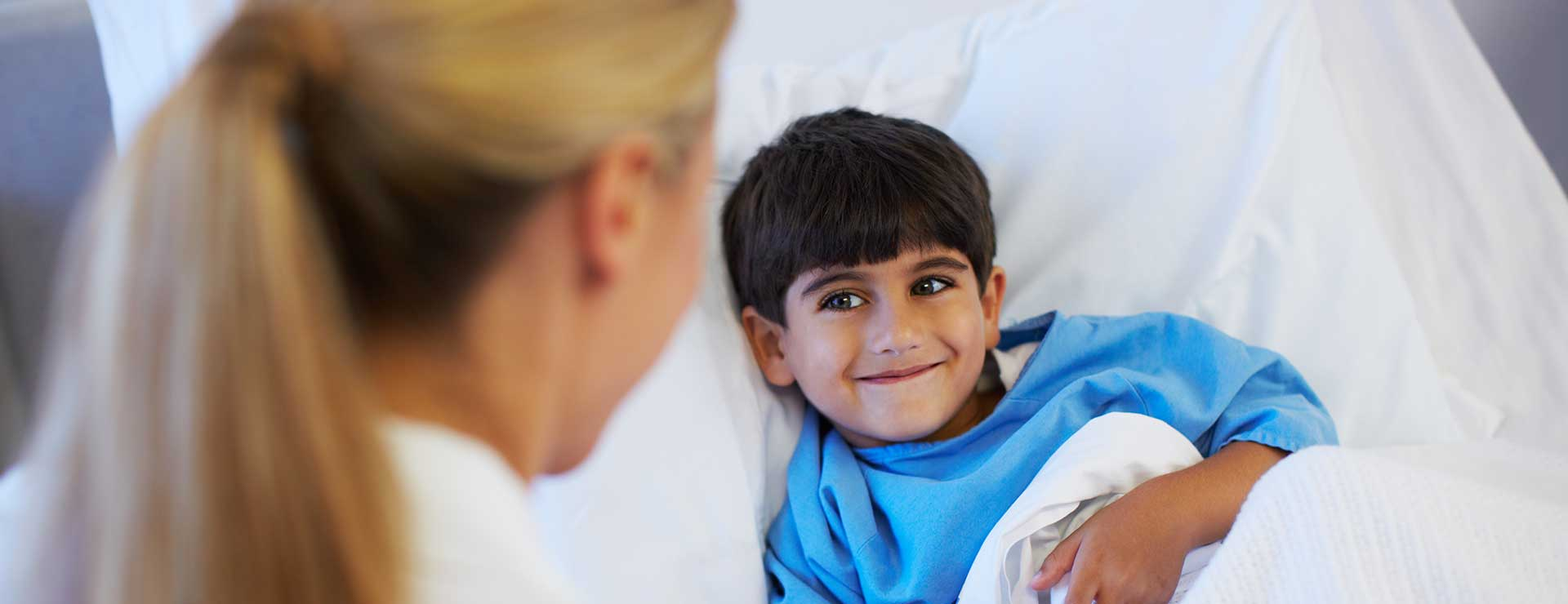 A child smiles at his doctor from his hospital bed.