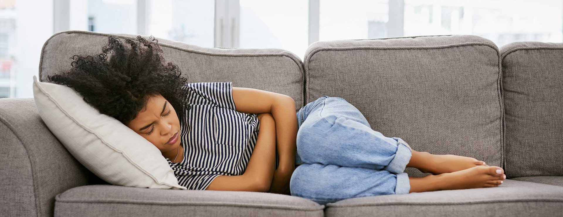 A young woman lays on her side on the couch, clutching her stomach in pain.