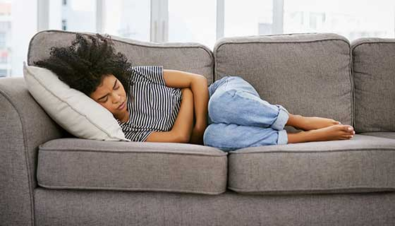 A woman lays on the couch, hugging her stomach in pain.