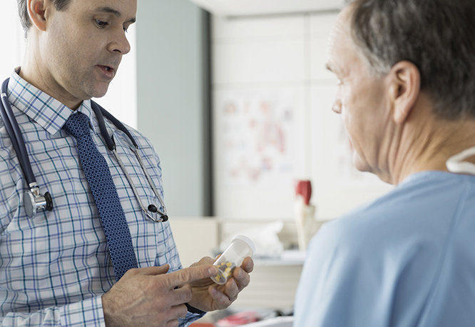 patient talking to physician holding pill bottle