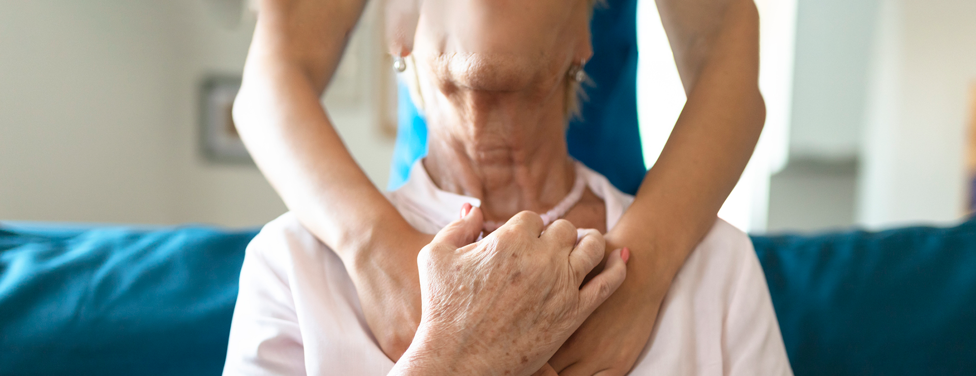 caregiver hugging senior patient
