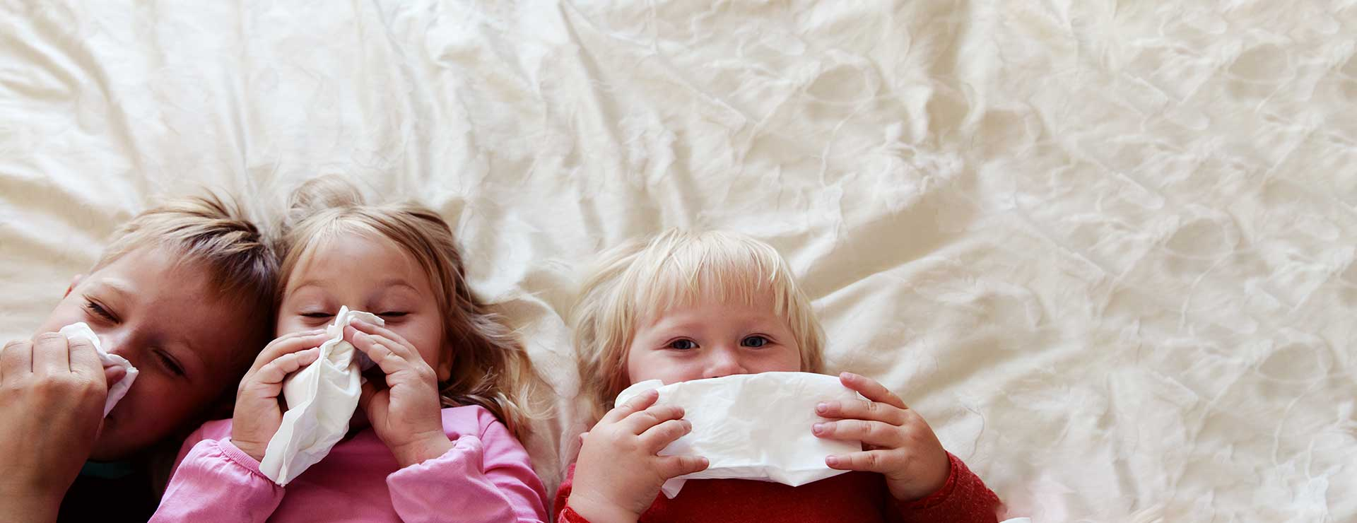 Children blow their noses, sick in bed.