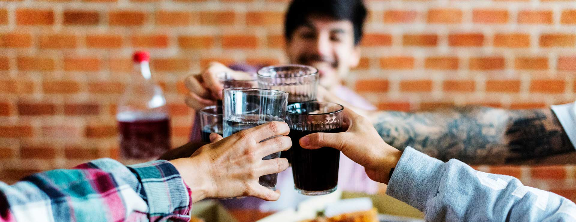 A group of friends clink their glasses of soda together over pizza.